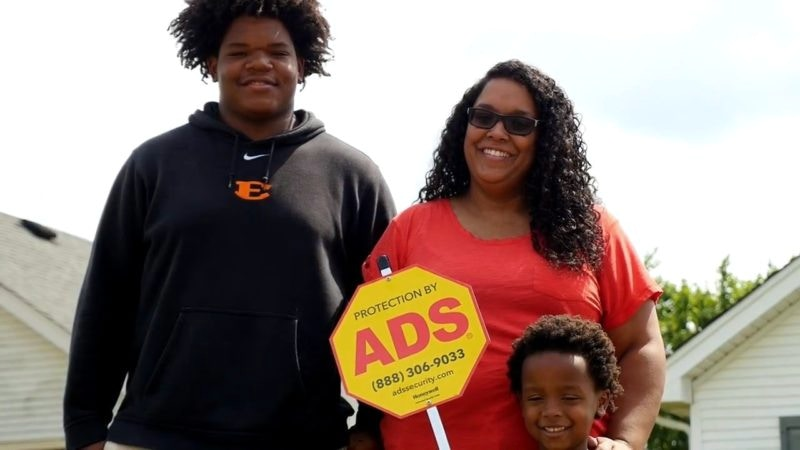 Family of 3 Smiling with ADS Security Sign